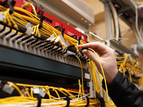Hand connecting the Fibre Optic Cable to the server